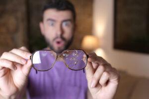 Man holding broken glasses